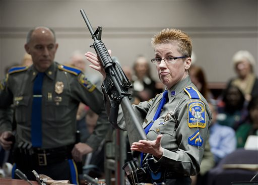 Detective Barbara J. Mattson, of the Connecticut State Police, holds up a Bushmaster AR-15 rifle  (AP Photo/Jessica Hill, File)