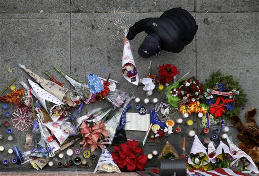 A man leaves flowers at an impromptu memorial near the site where two police officers were killed the day before in the Brooklyn borough of New York, Sunday  (AP Photo/Seth Wenig)
