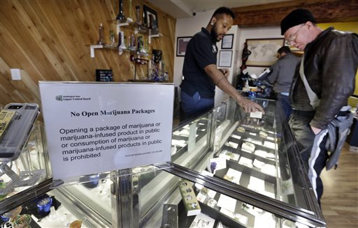 Cannabis City clerk Will Bibbs, left, helps a customer looking over a display case of marijuana products at the shop in Seattle.  (AP Photo/Elaine Thompson)