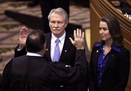 Oregon Gov. John Kitzhaber, middle, is joined by his fiancee,  Cylvia Hayes,(AP Photo/Don Ryan)