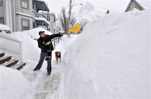 Lee Anderson adds to the pile of snow beside the sidewalk in front of his house in Somerville, Mass. (AP Photo/Josh Reynolds)