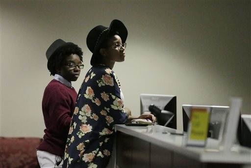 Shanté Wolfe, left, and Tori Sisson, right, wait for their marriage license to be processed before becoming the first couple to file their marriage license in Montgomery, Ala.  (AP Photo/Brynn Anderson)