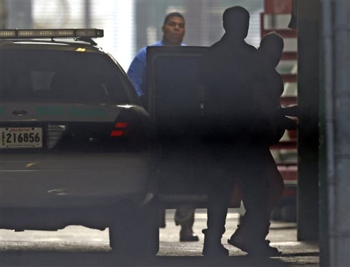 Robert Durst, far right, photographed through fencing, is escorted into Orleans Parish Criminal District Court through a tunnel entrance, in New Orleans.  (AP Photo/Gerald Herbert)