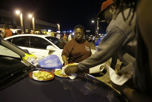 "Cat Daniels puts out snacks as smaller group of protesters gather along West Florissant Avenue in Ferguson, Mo., Tuesday, Aug. 11, 2015. The St. Louis suburb has seen demonstrations for days marking the anniversary of the death of 18-year-old Michael Brown, whose shooting death by a Ferguson police officer sparked a national ""Black Lives Matter"" movement. Tuesday was the fifth consecutive night a crowd gathered on West Florissant. (AP Photo/Jeff Roberson)"