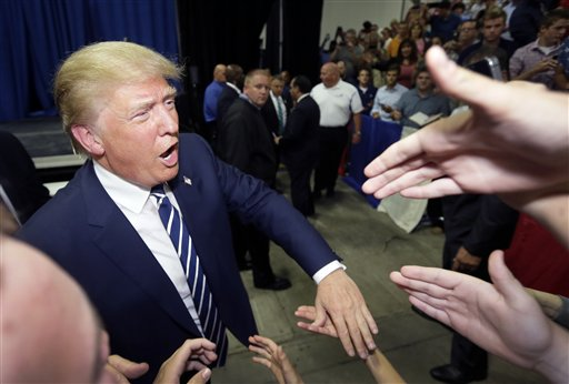 Republican presidential candidate Donald Trump meets supporters after addressing a GOP fundraising event, Tuesday, Aug. 11, 2015, in Birch Run, Mich. Trump attended the Lincoln Day Dinner of the Genesee and Saginaw county Republican parties. (AP Photo/Carlos Osorio)
