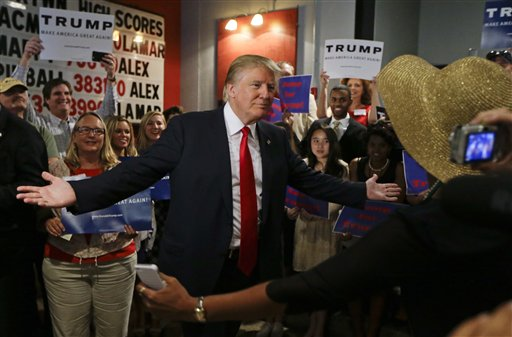 Republican presidential candidate Donald Trump reaches out to hug a supporter after he spoke at the National Federation of Republican Assemblies on Saturday, Aug. 29, 2015, in Nashville, Tenn. (AP Photo/Mark Humphrey)