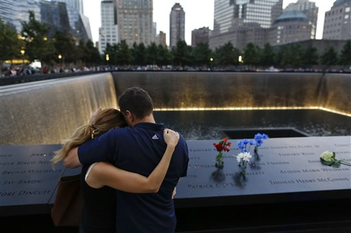 FILE- In this Sept. 11, 2014 file photo, David Pykon, right, and his fiancé Shelli Scrimale embrace while observing the 13th anniversary of the attacks on the World Trade Center at the north pool of the memorial in New York. Pykon's brother, Edward Pykon, was killed during the Sept. 11 attacks in 2001. Nearly a decade and a half after hijacked planes hit the World Trade Center's twin towers, the Pentagon and a field near Shanksville, Pennsylvania, the anniversary continues to be marked with observances around the country. (AP Photo/Julie Jacobson, File)