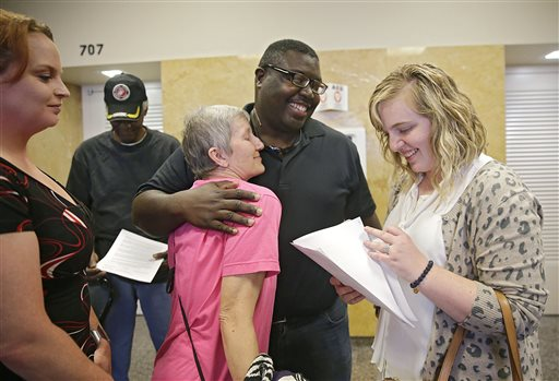 Marq Lewis, center, receives a hug from Peggy Pianalto as Nicole Dust-Neil reads over indictments returned by a Grand Jury against Tulsa County Sheriff Stanley Glanz Wednesday, Sept. 30, 2015, in Tulsa, Okla. Dust-Neil works for the attorney that represented We the People Oklahoma. At left are Geana Newman and Edward Jones both supporters of We the People Oklahoma. Glanz quickly decided to resign Wednesday after being indicted by a grand jury that investigated his office following the fatal shooting of an unarmed man by a volunteer deputy who said he mistook his handgun for a stun gun. (Mike Simons/Tulsa World via AP) ONLINE OUT; KOTV OUT; KJRH OUT; KTUL OUT; KOKI OUT; KQCW OUT; KDOR OUT; TULSA OUT; TULSA ONLINE OUT; MANDATORY CREDIT