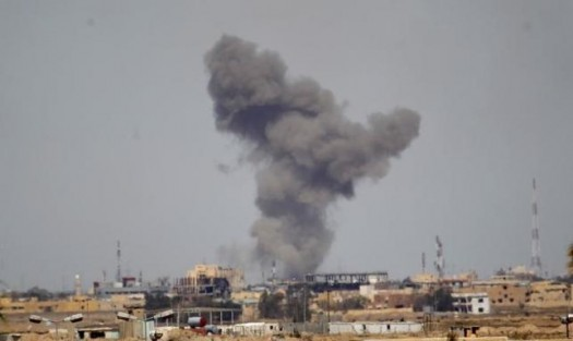 A plume of smoke rises above a building during an air strike in Tikrit March 27, 2015. REUTERS/Thaier Al-Sudani