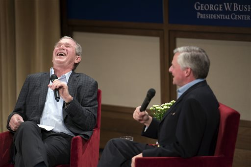 Former President George W. Bush, left, reacts to a joke during a conversation Sunday, Nov. 8, 2015, with Pulitzer Prize winning author Jon Meacham, right, about Meacham's biography of Bush's father former President George Herbert Walker Bush's at the George W. Bush Presidential Center in Dallas. (AP Photo/Jeffrey McWhorter)