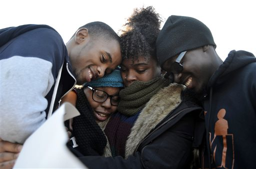 Members of Concerned Student 1950 embrace after the announcement that University of Missouri System President Tim Wolfe would resign Monday, Nov. 9, 2015, in Columbia, Mo. Wolfe resigned Monday with the football team and others on campus in open revolt over his handling of racial tensions at the school. (Halee Rock/Missourian via AP) MANDATORY CREDIT CREDIT