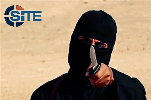 """This image made from militant video, which has been verified by SITE Intel Group and is consistent with other AP reporting, shows Mohammed Emwazi , known as """"Jihadi John,"""" holding a knife. A U.S. drone strike targeted a vehicle in Syria believed to be transporting the masked Islamic State militant known as """"Jihadi John"""" on Thursday, Nov. 12, 2015 according to American officials. Whether the strike killed the British man who appears in several videos depicting the beheadings of Western hostages was not known, officials said. (SITE Intel Group via AP)"""