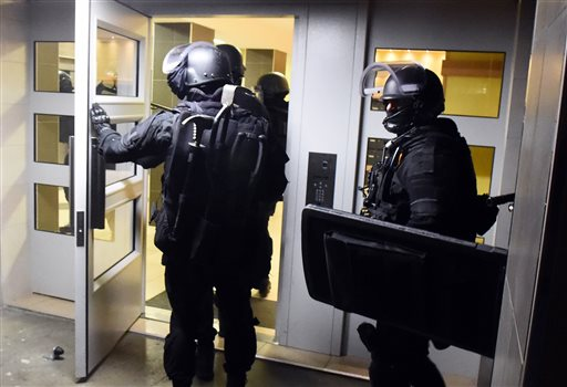 Anti terrorism police officers enter a building during a raid in the Mirail district in Toulouse, southwestern France, Monday, Nov. 16, 2015. France's Prime Minister Manuel Valls says there have been 150 police raids overnight in the country. (AP Photo) FRANCE OUT