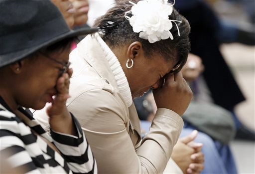 Jamar Clark's sister, Danielle Burns, right, grieves as she and other family members gathered during a news conference held by the Minneapolis Urban League, Wednesday, Nov. 18, 2015, in Minneapolis. Jamar Clark was shot and killed by a Minneapolis police officer during an apparent struggle with police on Sunday. (AP Photo/Jim Mone)
