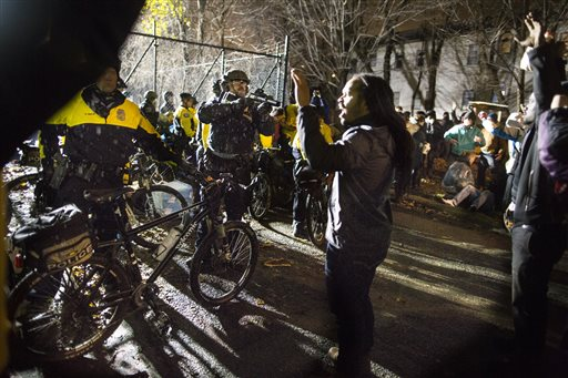In this Wednesday, Nov. 18, 2015 photo, Jeremiah Ellison, center right, son of U.S. Rep. Keith Ellison, stands near police during a protest at the Minneapolis Police Department 4th Precinct building in Minneapolis. People were protesting the fatal shooting of Jamal Clark by Minneapolis police on Sunday. (Renee Jones Schneider/Star Tribune via AP)  MANDATORY CREDIT; ST. PAUL PIONEER PRESS OUT; MAGS OUT; TWIN CITIES LOCAL TELEVISION OUT