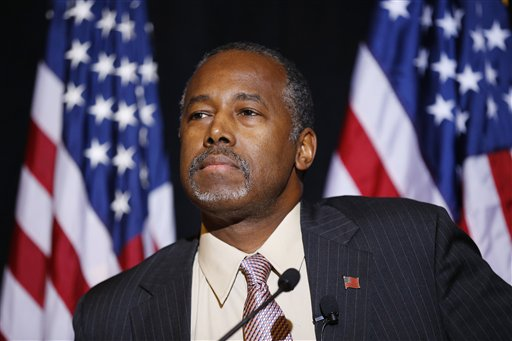 In this Nov. 16, 2015 photo, Republican presidential candidate Dr. Ben Carson speaks at a news conference in Henderson, Nev.  Carson is making a post-Thanksgiving trip to visit Syrian refugees in Jordan this weekend.  This trip comes as Carson struggles to command foreign policy, as it becomes a greater focus in the 2016 contest.  Those close to him concede his foreign policy fluency isn't yet where it needs to be.   (AP Photo/John Locher)