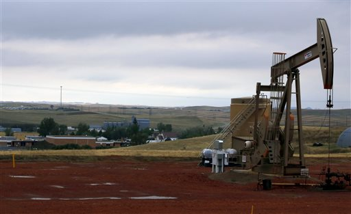 In this Sept. 5, 2015, photo, a pump jack pumps oil on a hill above Alexander, N.D, and the town's school.  The U.S., seemingly awash in crude oil after an energy boom sent thousands of workers scurrying to the plains of Texas and North Dakota, will begin exporting oil for the first time since the 1973 oil embargo. (AP Photo/Martha Irvine)