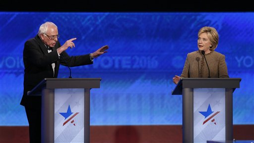 Bernie Sanders, left, and Hillary Clinton speak during an exchange during the Democratic presidential primary debate Saturday, Dec. 19, 2015, at Saint Anselm College in Manchester, N.H. (AP Photo/Jim Cole)