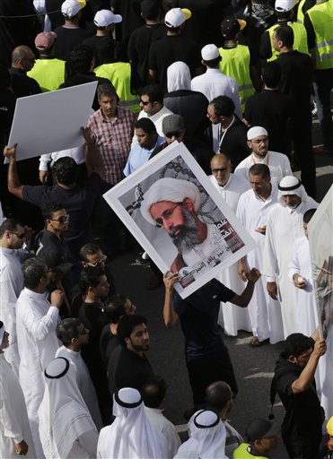 In this Saturday, May 30, 2015, photo, Saudis carry a poster demanding freedom for jailed Shiite cleric Sheikh Nimr al-Nimr, during a funeral procession, in Tarut, Saudi Arabia. Saudi Arabia says it has executed 47 prisoners, including leading Shiite cleric Sheikh Nimr al-Nimr. The cleric's name was among a list of the 47 prisoners executed carried by the state-run Saudi Press Agency. It cited the Interior Ministry for the information. (AP Photo/Hasan Jamali)