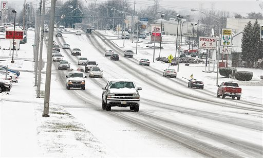 Traffic moves slowly along Hall Road Wednesday, Jan. 20, 2016, as snow falls making roads slippery, in Alcoa, Tenn. As the South and East braced for a nor'easter with the potential for significant snowfall by week's end, snow began to blanket much of Kentucky and Tennessee and contributed to at least one traffic-related death Wednesday. (Tom Sherlin /The Daily Times via AP) MANDATORY CREDIT