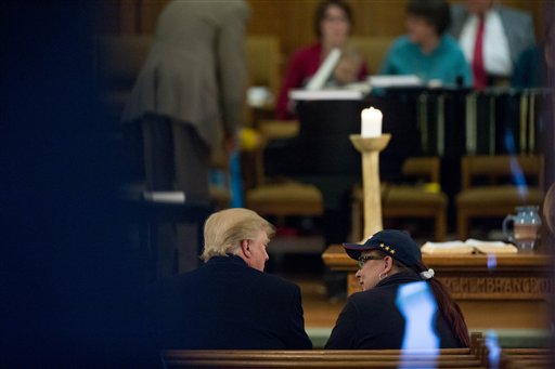 Republican presidential candidate Donald Trump, left, speaks with a woman as he arrives for service at First Presbyterian Church in Muscatine, Iowa, Sunday, Jan. 24, 2016. Trump will be holding a rally at Muscatine High School in the afternoon. (AP Photo/Andrew Harnik)