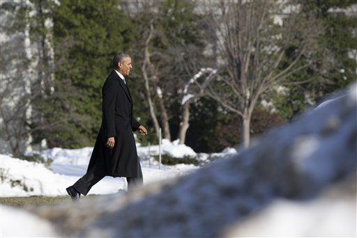 President Barack Obama walks past piled snow toward the South Lawn of the White House in Washington, Monday, Jan. 25, 2016, to board Marine One en route to Walter Reed National Military Medical Center in Bethesda, Md., to visit with wounded service members. (AP Photo/Carolyn Kaster)