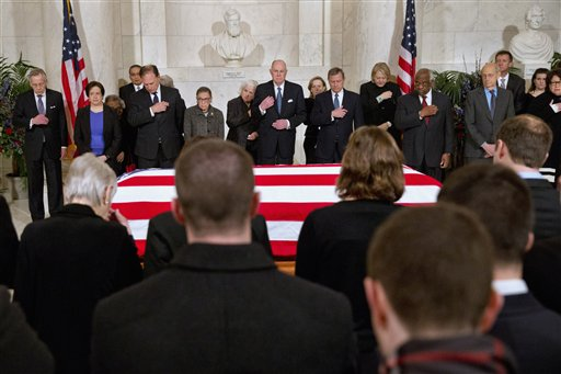 Supreme Court Justices make the sign of the cross during prayers at a private ceremony in the Great Hall of the Supreme Court in Washington, Friday, Feb. 19, 2016, where late Supreme Court Justice Antonin Scalia lies in repose. In back, from left are, Counselor to the Chief Justice Jeffrey Minear, and Supreme Court Justices Elena Kagan, Samuel Anthony Alito, Jr., Ruth Bader Ginsburg, Anthony Kennedy, Chief Justice John Roberts, Jr., Clarence Thomas, Stephen Breyer, and Sonia Sotomayor. (AP Photo/Jacquelyn Martin, Pool)