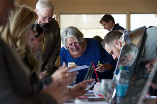 Republican District 25 Chair Rebecca Mahaney looks over paperwork in a presidential polling place Tuesday, March 1, 2016 in Anchorage, Alaska. Alaska Republicans are poised to decide which of the remaining GOP presidential candidates will get their support. (AP Photo/Michael Dinneen)