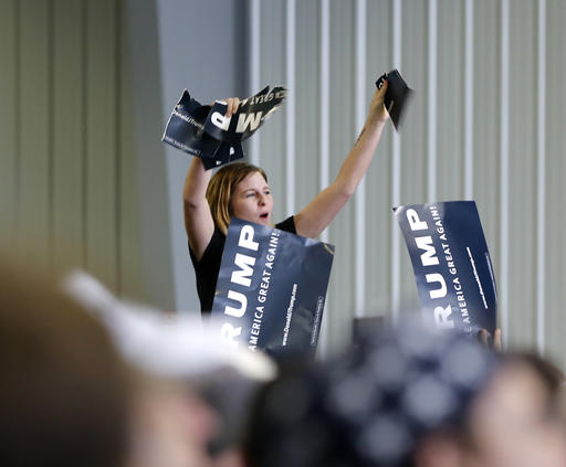 A protester tears up a campaign sign for Republican presidential candidate Donald Trump during a rally Sunday, March 13, 2016, in Bloomington, Ill. (AP Photo/Charles Rex Arbogast)