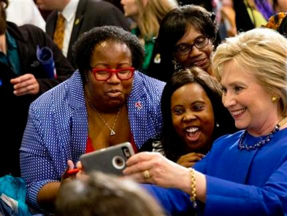 FILE - In this Feb. 23, 2016 file photo, Democratic presidential candidate Hillary Clinton takes pictures with supporters after a campaign event at the Central Baptist Church in Columbia, S.C. During a primary season that has proved surprisingly competitive, bombarded with persistent critiques about her likeability and trustworthiness, Clinton has maintained a strong bond with one significant block of Democratic Party voters. Black women. (AP Photo/Jacquelyn Martin, File)