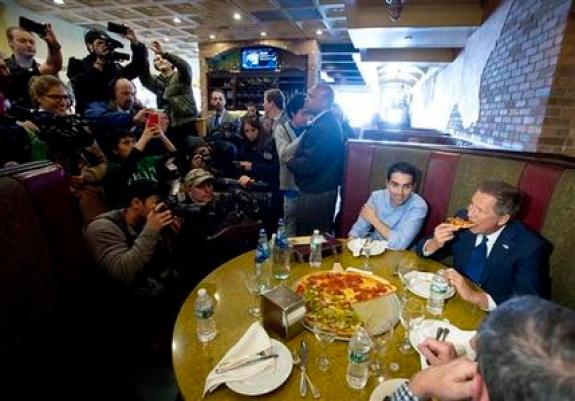 Republican presidential candidate, Ohio Gov. John Kasich, right, eats with  local party members in Gino's Pizzeria in the Queens borough of New York, Wednesday, March 30, 2016, while being watched by the media. The three Republican presidential candidates now say they aren't committing to supporting whomever the party chooses as its nominee for the November election, which could lead to a messy and fractured nominating convention in July. (AP Photo/Mark Lennihan)