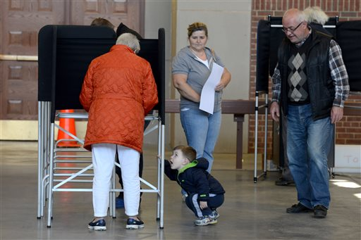 Elmir Nuhanovic, center, crouches down on the floor as his grandfather, Ekrem Nuhanovic watches over him during voting for the New York presidential primaries at the Utica Armory Tuesday, April 19, 2016, in Utica, N.Y. (Tina Russell/Observer-Dispatch via AP)