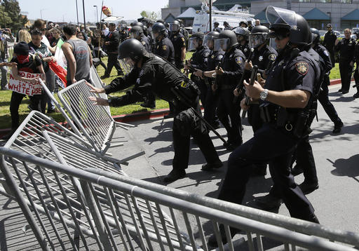 Police officers push down barricades used by a group protesting Republican presidential candidate Donald Trump outside of the Hyatt Regency hotel during the California Republican Party 2016 convention in Burlingame, Calif., Friday, April 29, 2016. (AP Photo/Eric Risberg)