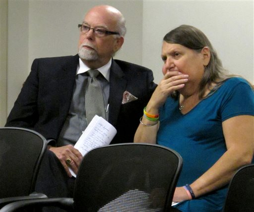 Pedro Irigonegaray, left, a Topeka, Kansas, attorney, and Stephanie Mott, right, a transgender Topeka woman, follow comments during a public hearing on a proposed regulatory change from the state health department that would make it harder to change the gender listed on a person's birth certificate, Thursday, May 12, 2016, in Topeka, Kan. Irigonegaray and Mott consider the change unnecessary and mean-spirited. (AP Photo/John Hanna)