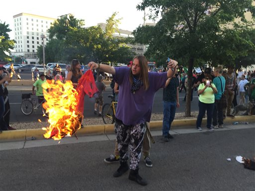 A protestor of Republican presidential candidate Donald Trump holds a burning T-shirt as hundreds of people protest outside a rally for Trump in Albuquerque, Tuesday, May 24, 2016. (AP Photo/Russell Contreras)