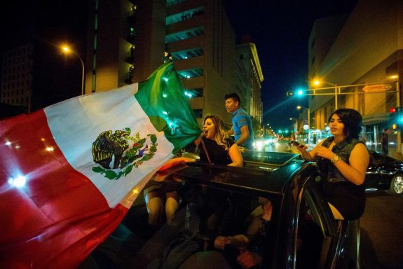 In this May 24, 2016, photo, a woman waves the Mexican flag while driving past the Albuquerque Convention Center after a rally by Republican presidential candidate Donald Trump in Albuquerque, N.M. Hispanic voters in Florida, New Mexico and California have waved Mexican flags and bashed Donald Trump piñatas to protest the Republican presidential contender's hard line approach to immigration. Yet far from the protests, an increasingly vocal Hispanic minority is speaking out in favor of the brash billionaire.  (Jett Loe/The Las Cruces Sun-News via AP) MANDATORY
