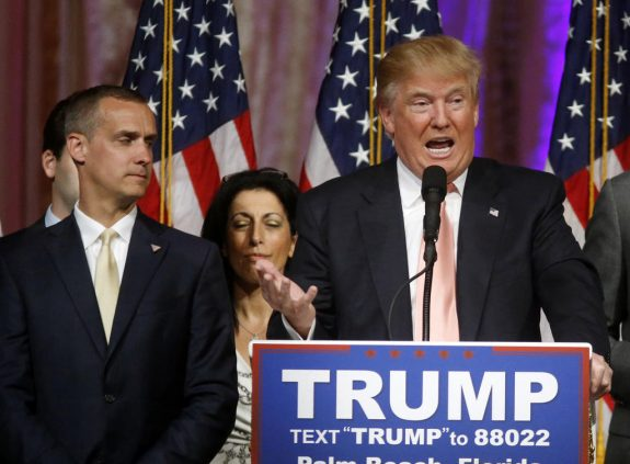 FILE - In this March 15, 2016, file photo, Republican presidential candidate Donald Trump speaks to supporters at his primary election night event at his Mar-a-Lago Club in Palm Beach, Fla., as campaign manager Corey Lewandowski listens at left. Trump's penchant for encouraging rivalries and pitting even those closest to him against each other is roiling his Republican presidential campaign as he plunges into the general election. The tensions boiled over last week with the abrupt ouster of political director Rick Wiley, who left the campaign after just six weeks. (AP Photo/Gerald Herbert, File)