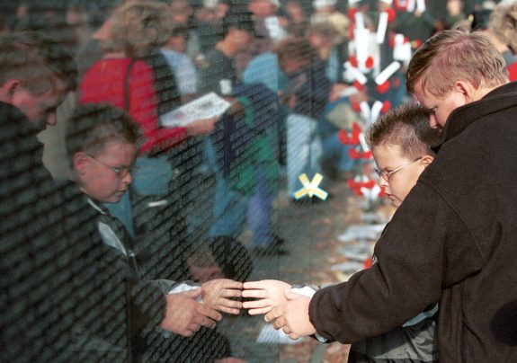 Remembering: A son and grandson remember their father and grandfather at the Vietnam War Memorial in Washington, DC. (Photo by Doug Thompson)