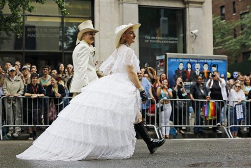 Scott Parent, left, and Tigger! Ferguson, wearing a wedding dress, parade down Fifth Avenue during the Heritage Pride March in New York. (AP Photo/Kathy Willens)