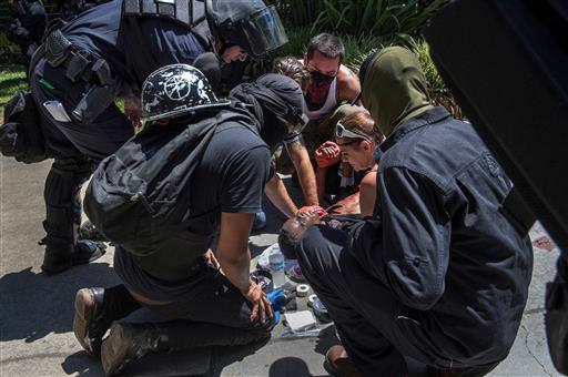 A victim is attended after he was stabbed during a rally at the State Capitol in Sacramento, Calif. (Rene C. Byer/The Sacramento Bee via AP)
