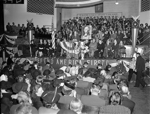 "This Oct. 3, 1941, file photo shows a crowd of over 4,000 people filled the Gospel Tabernacle in Fort Wayne, Ind., to hear Col. Charles Lindbergh, seen on the speaker's stand in the center, address a rally of the America First Committee. Presumptive Republican presidential nominee Donald Trump boils down his foreign policy agenda to two words: ""America First."" For students of U.S. history, that slogan harkens back to the tumultuous presidential election of 1940, when hundreds of thousands of Americans joined the anti-war America First Committee. That isolationist group's primary goal was to keep the United States from joining Britain in the fight against Nazi Germany, which by then had overrun nearly all of Europe. But the committee is also remembered for the unvarnished anti-Semitism of some of its most prominent members and praise for the economic policies of Adolf Hitler. (AP Photo/File)"