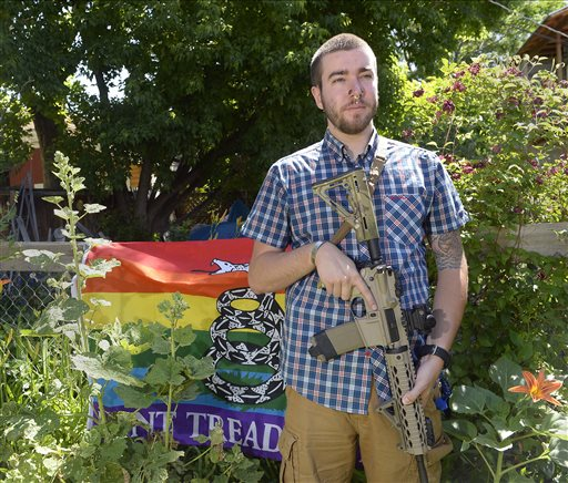 Matt Schlentz poses with his Rainbow-Gadsen Flag and AR-15 in his backyard in Salt Lake City, Wednesday, June 16. Schlentz is the Pink Pistols Utah chapter President and said Pink Pistols, a national LGBT pro-gun rights organization, membership has grown from 1,500 to 4,000 since Omar Mateen's June 12 rampage in Orlando, Fla. (Al Hartmann/The Salt Lake Tribune via AP)