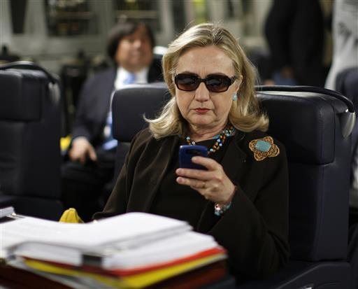 hen-Secretary of State Hillary Rodham Clinton checks her Blackberry from a desk inside a C-17 military plane upon her departure from Malta. (AP Photo/Kevin Lamarque)