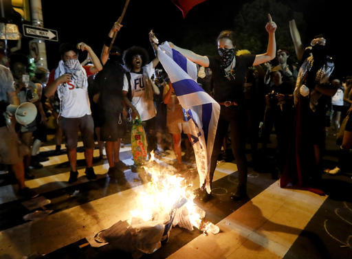 Demonstrators burn a flag during a protest in Philadelphia, Tuesday, July 26, 2016, during the second day of the Democratic National Convention. (AP Photo/John Minchillo)