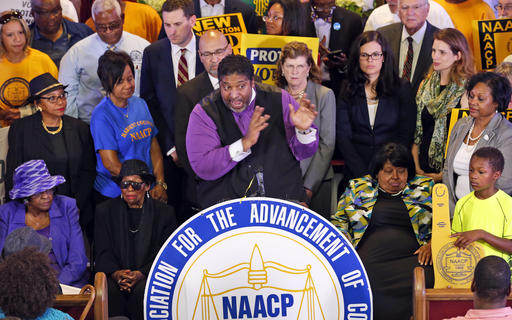 File-This June 21, 2016, file photo shows North Carolina NAACP president, Rev. William Barber, center at podium gesturing during a news conference in Richmond, Va. A federal appeals court on Friday, July 29, 2016, blocked a North Carolina law that required voters to produce photo identification and follow other rules disproportionately affecting minorities, finding that the law was intended to make it harder for blacks to vote in the presidential battleground state. Rev. Barber, said in an interview that the ruling was a powerful victory for civil rights and for democracy.  (AP Photo/Steve Helber, File)