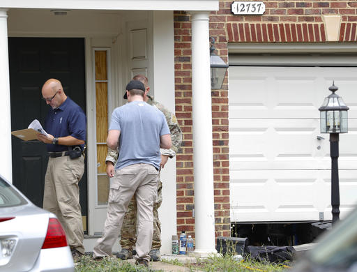 Law enforcement officers stand outside the home of Nicholas Young, a Washington Metro Transit Officer, Wednesday, Aug. 3, 2016, in Fairfax, Va., Young was arrested at Metro's headquarters in Washington and charged with a single count of attempting to provided material support to a terrorist group. (AP Photo/Pablo Martinez Monsivais)