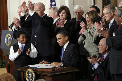 FILE - In this March 23, 2010, file photo President Barack Obama is applauded after signing the Affordable Care Act into law in the East Room of the White House in Washington. Government cost estimates for expanding Medicaid to millions more low-income people are increasing faster than expected, raising questions about a vital part of President Barack Obama's health care law. Estimated per-person costs were an eye-catching 49 percent higher than previously calculated, according to a recent report to Congress from nonpartisan experts with the federal Centers for Medicare and Medicaid Services. The new estimate of $6,366 per person for 2015 was nearly $2,100 higher than expected.(AP Photo/Charles Dharapak, File)