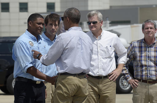 President Barack Obama is greeted by, from left, Rep. Cedric Richmond, D-La., Rep. Garret Graves, R-La., Sen. Bill Cassidy, R-La., and Sen. David Vitter, R-La. after arriving on Air Force One at Baton Rouge Metropolitan Airport in Baton Rouge, La., Tuesday, Aug. 23, 2016. Obama is traveling to the area to survey the flood damage. (AP Photo/Susan Walsh)