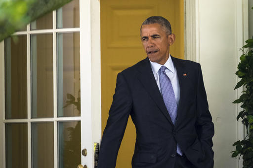 President Barack Obama steps out of the Oval Office of the White House in Washington, Friday, Aug. 26, 2016, as he departs  for a quick trip to Walter Reed National Military Medical Center in Bethesda, Md to visit with wounded service members.  (AP Photo/J. David Ake)