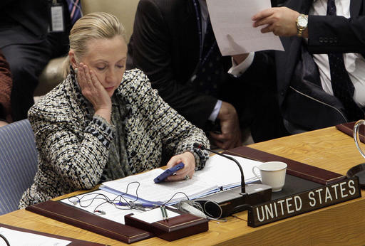 FILE - In this March 12, 2012, file photo, then-Secretary of State Hillary Clinton checks her mobile phone after her address to the Security Council at United Nations headquarters. In a rare step, the FBI on Friday, Sept. 2, 2016,  published scores of pages about confidential interviews with Hillary Clinton and others from its recently closed investigation into the former secretary of state's use of a private email server.. (AP Photo/Richard Drew, File)
